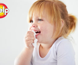 Toddler girl holding tissue to her nose