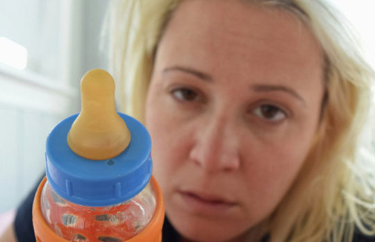 Tired mum with bottle