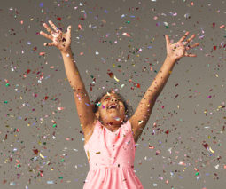 Happy young girl with hands in the air with confetti