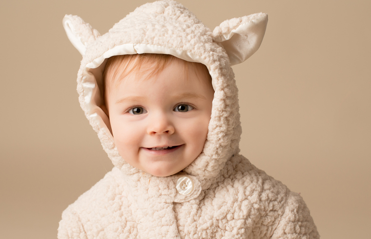 Cute toddler in a hooded sheep jacket
