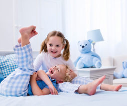 siblings playing on the bed