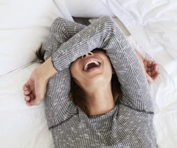 Woman covering her eyes laughing lying on a bed feature