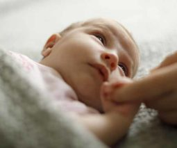 Newborn baby holding parent's hand