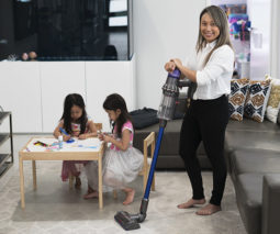 Mum and girls using Dyson vacuum cleaner
