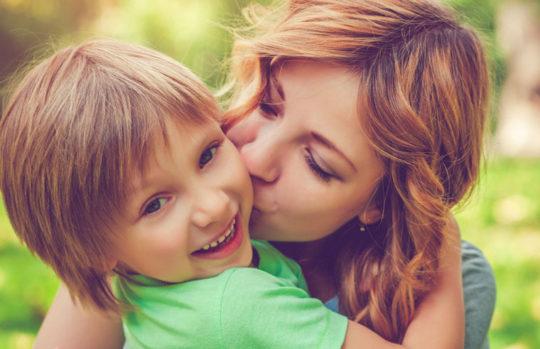 Mum cuddling happy boy