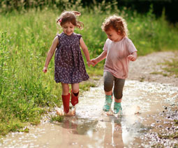 Girls wearing gumboots walking in puddle