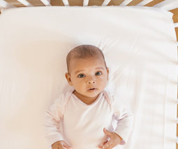 Baby lying awake in cot feature