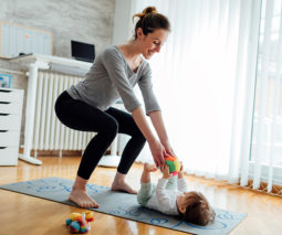 Mother exercising with baby in nursery feature