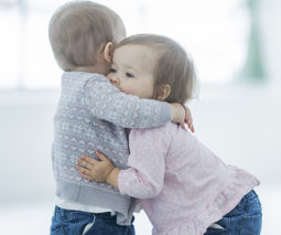 toddler boy and girl hugging feature