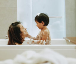 Mother and toddler son in bath together