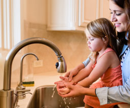 Mother and daughter washing hands in kitchen