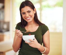 Woman standing in kitchen eating bowl of cereal