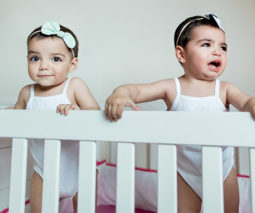 Twin girls standing up in the cot