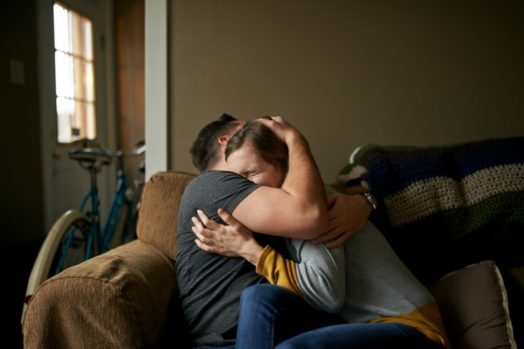 Couple hugging on couch sad