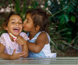Two Aboriginal girls laughing and kissing