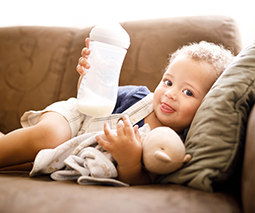 Toddler boy lying on couch holding bottle of milk