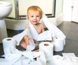 Toddler sitting in toilet paper