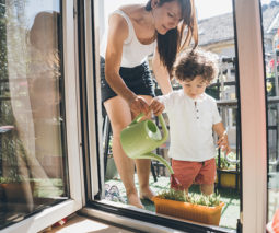Mother with toddler with watering can on balcony feature