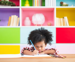 Preschool child writing in book doing school work at home