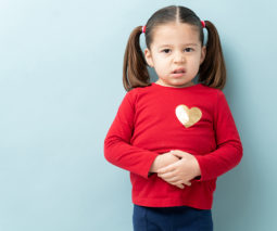 Toddler girl holding tummy ache feature