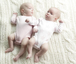 Twin baby girls in onesies lying on blanket feature