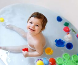 Toddler in bath with toys smiling - feature