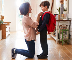 Mother kneeling down to school child in uniform at home - feature