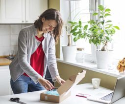 Woman opening package in kitchen with laptop - feature