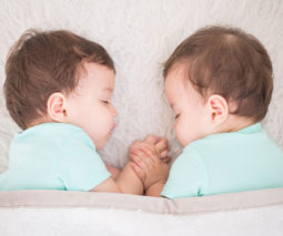 Baby twins asleep holding hands with dummies in their mouths