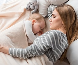 Mother asleep with baby on the bed