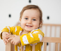 Toddler standing up smiling in cot