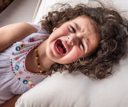 Young girl crying in bed