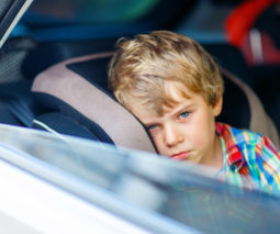 Child in carseat looking sad