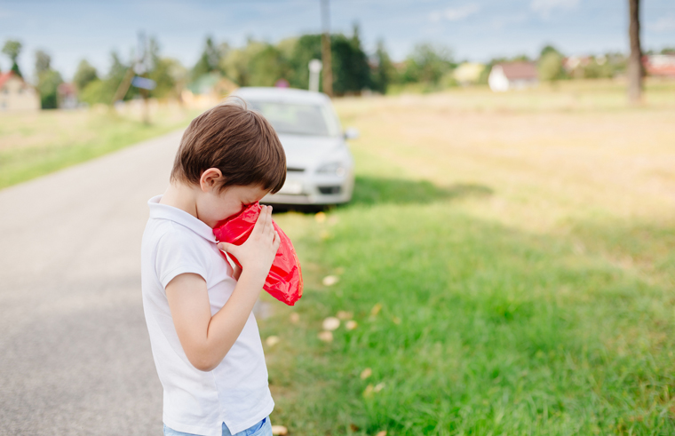 Child using sick bag by the side of the road - car sickness