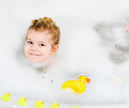 Toddler girl in bath with bubbles and toy ducks - thumbnail