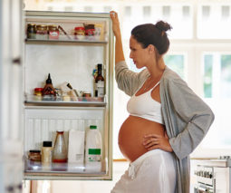 Pregnant woman standing in front of open fridge - feature