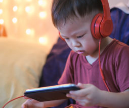 Asian boy toddler watching smartphone with headphones on - feature