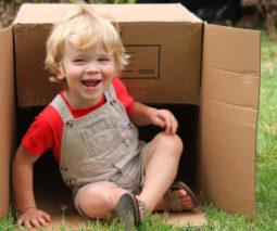 Toddler sitting in cardboard box