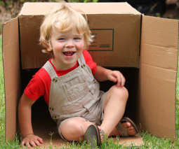 Toddler sitting in cardboard box