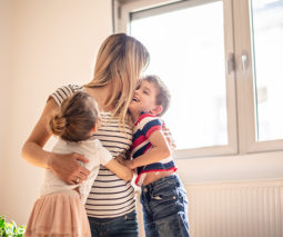 Mum hugging her two kids in an empty room