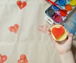 Child hand holding potato heart shaped stamp with paper and paints