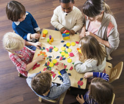 Teacher with children at childcare - feature