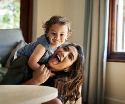 Toddler leaning over laughing mother - feature