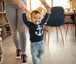 Walking baby with dummy in mouth and holding mother's hands - feature
