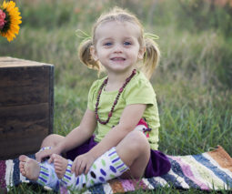 young girl wearing leg warmers sitting on rug outdoors - feature
