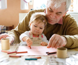 Baby girl sitting in grandfather's lap drawing - feature