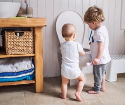 Two boys toddler and baby playing with toilet - feature