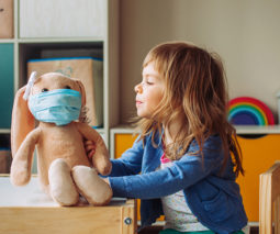 Young girl playing with a toy with a face mask on - feature