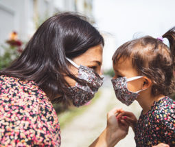 Mother and young girl wearing reusable face masks - feature