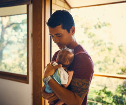 New father holding newborn baby - feature